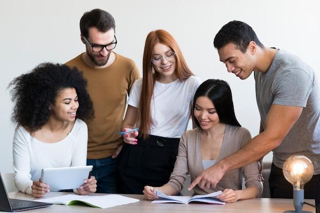 Gruppe positiver junger menschen, die zusammenarbeiten