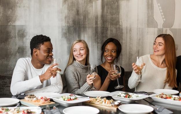Gruppe positiver menschen, die zusammen zu abend essen