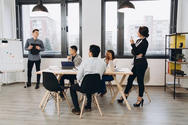 Gruppe positiver multikultureller marketingexperten, die den arbeitsprozess planen und ideen austauschen, während sie eine werbekampagne erstellen. junge kollegen, die im loft-innenbüro zusammenarbeiten