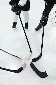 Gruppe professioneller hockeyspieler in sportuniform, handschuhen und schlittschuhen, die im kreis auf der eisbahn stehen und ihre stöcke in der mitte halten