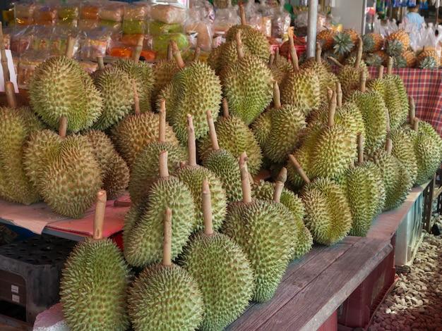 Gruppe reifer durian auf hölzernem regal am obstmarkt kaufen.
