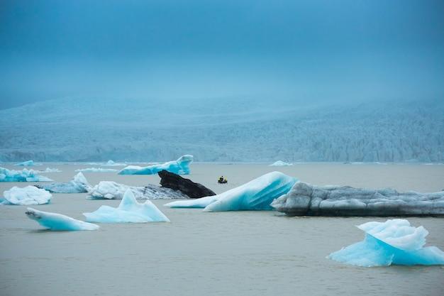 Gruppe reisende nehmen ein boot an jokulsarlon-gletscherlagune, island