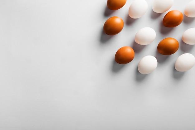Gruppe rohe eier weiß und braun. konzept der vielfalt, isolation, rassismus, ungleichheit. auf grauem hintergrund. draufsicht, exemplar