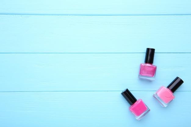 Gruppe rosa nagellacke auf blauem hintergrund