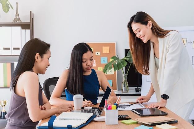 Gruppe schöne asiatinnen, die im büro zum diskussions- oder geistesblitzgeschäfts-startprojekt sich treffen.
