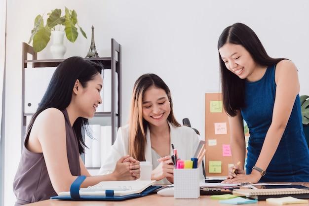 Gruppe schöne asiatinnen, die im büro zum diskussionsgeschäft sich treffen.