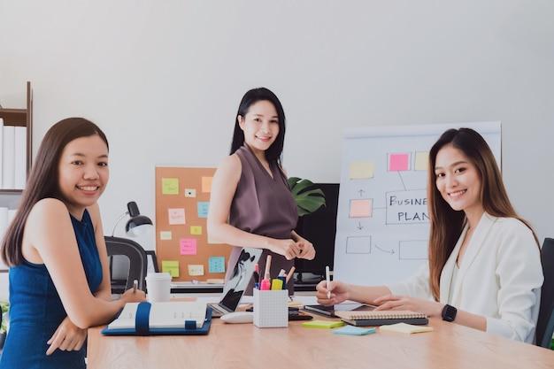 Gruppe schöne glückliche asiatinnen, die in den büroräumen zum diskussionsgeschäft sich treffen.
