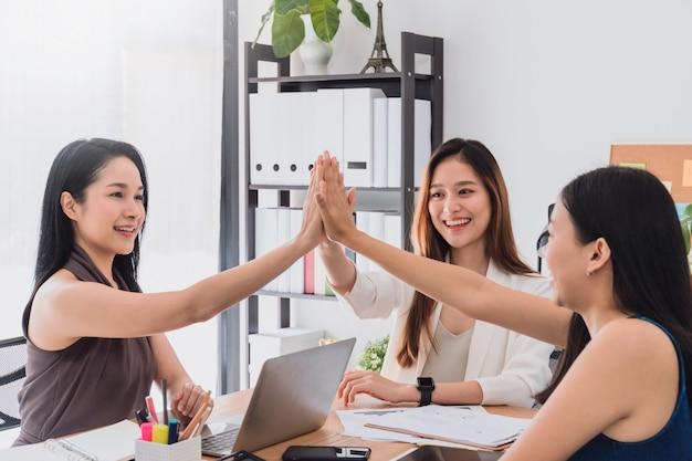 Gruppe schöne glückliche asiatinnen, die zusammen note des hochs fünf in den büroräumen zur diskussion treffen und geben oder firmenneugründungsprojekt gedanklich lösen.