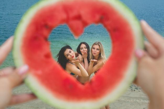 Gruppe schöne nette frauen, die bei der wassermelone auf dem strand liegen. lachende freundinnen auf der seeseite, die spaß haben. hübsche frauen, die einen luftkuß innerhalb des wassermelonenherzens bräunen und senden