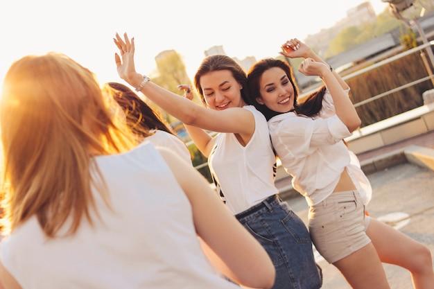 Gruppe schöne sorglose tanzende freundinnen haben spaß in der stadtstraße