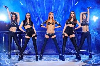Gruppe sexy Go-go-Tänzer, die schwarze Ausstattungen tragen