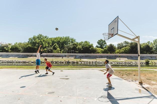 Gruppe spieler, der basketball am gericht draußen spielt
