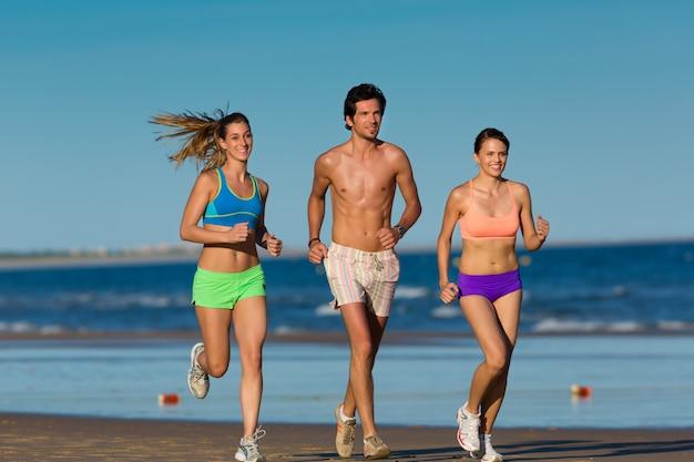 Gruppe sportleute - mann und frauen - rüttelnd auf dem strand