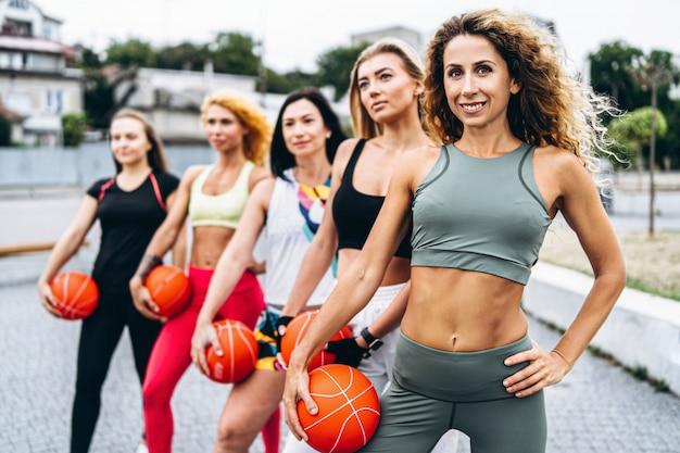 Gruppe sportliche frauen, die übungen mit orange bällen durchführen