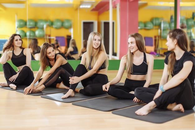Gruppe sportliche glückliche frauen, die auf dem turnhallenboden sitzen