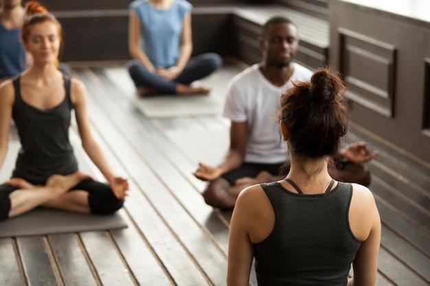 Gruppe sportliche leute in der einfachen sitzhaltung