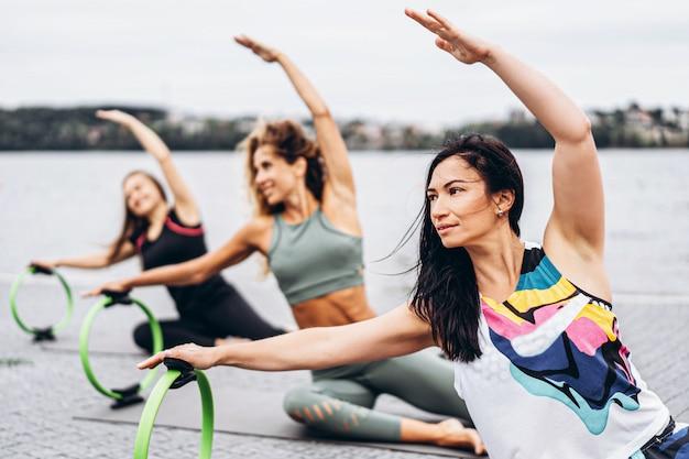 Gruppe sportlicher frauen, die dehnübungen mit einem speziellen sportkreis auf der straße nahe dem wasser tun.