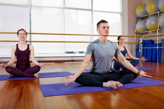 Gruppe sportlicher menschen, die auf matten sitzen und zur entspannung trainieren.