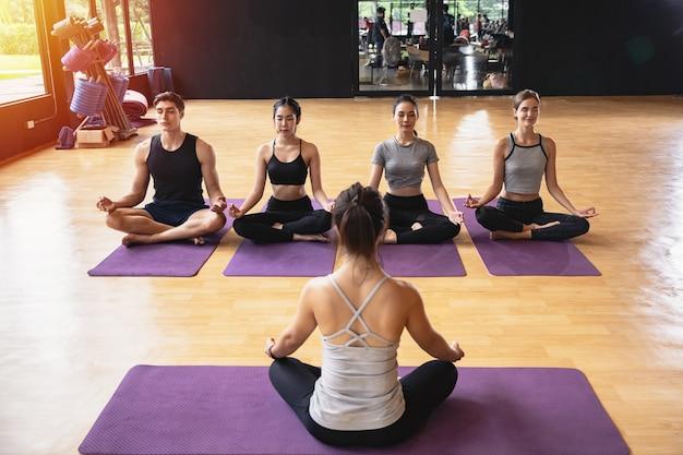 Gruppe sportlicher mix-rennen von kaukasischen und asiatischen menschen, sowohl frauen als auch männer, die yoga praktizieren, üben im studio-fitnessstudio, young trainer sitzen vorne. yoga und fitness erarbeiten gesundheitskonzept
