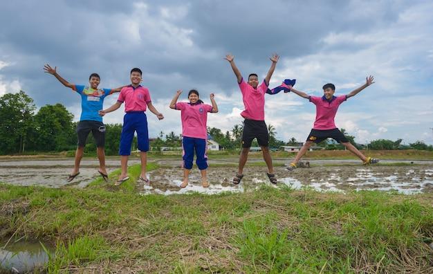 Gruppe studenten, die auf dem reisgebiet springen glücklicher junge und mädchen springen an reislandnatur landsc