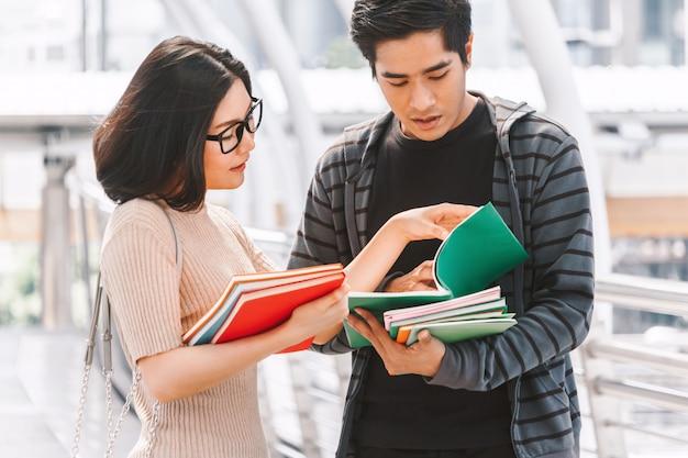 Gruppe studenten, die draußen notizbücher halten bildungskonzept