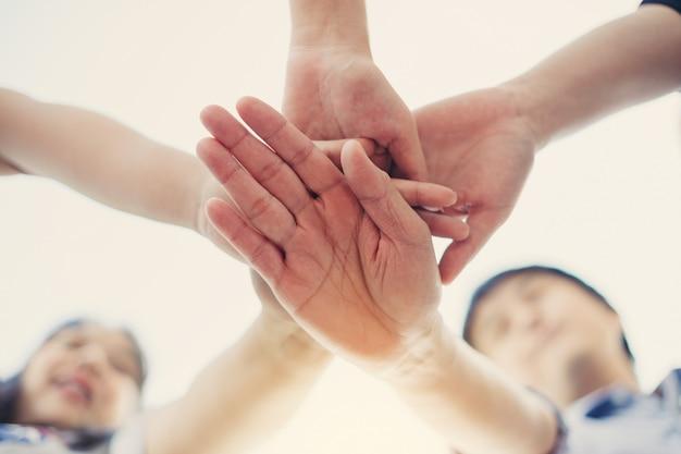 Gruppe studenten- oder geschäftsmannhände, die sich zusammen für teamwork- und geschäftszusammenarbeitskonzept anschließen.