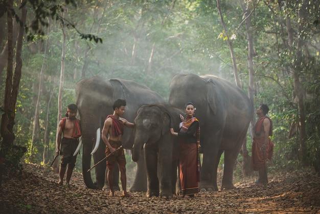 Gruppe thailändischer hirten im dschungel mit elefanten. historische lifestyle-momente aus der thailändischen kultur
