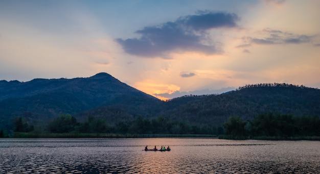 Gruppe touristen auf einem kajak schaufeln im verdammungsfluß mit berglandschaftsansicht