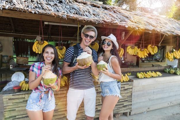 Gruppe touristen, die kokosnuss auf thailand-straßenmarkt, nettem mann und frauen in traditionellem trinken