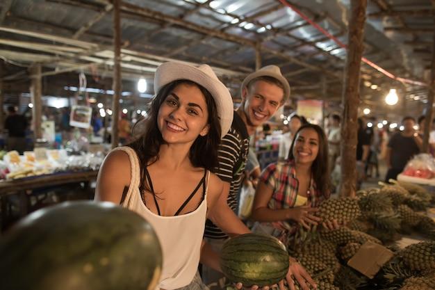 Gruppe touristen, die wassermelone auf straßenmarkt in jungen leuten kaufen, die frische früchte kaufen
