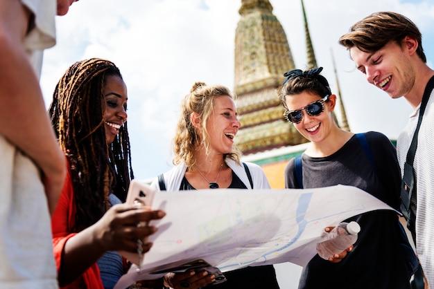 Gruppe touristen, welche die karte im thailändischen tempel verwenden