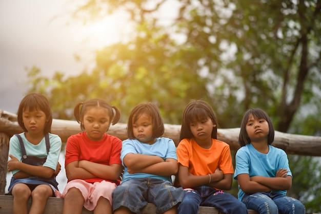 Gruppe traurige kinder, die auf dem park sitzen