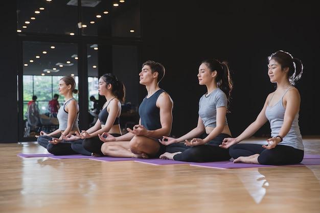 Gruppe übendes yoga der mischungsrassenleute, das zusammen für gesunden lebensstil im fitness-club meditiert