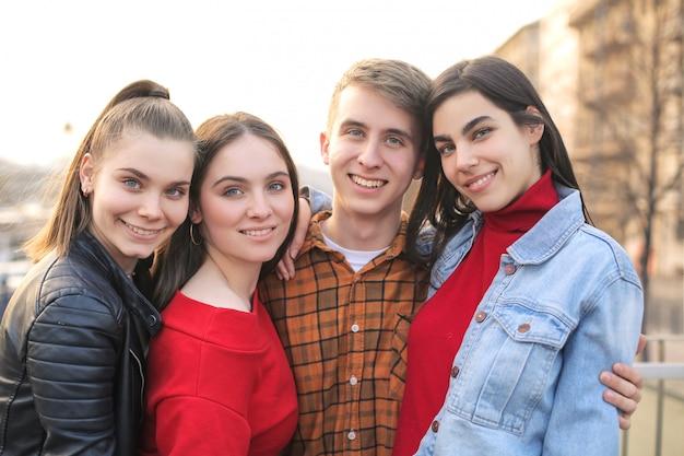 Gruppe umarmende und lächelnde freunde