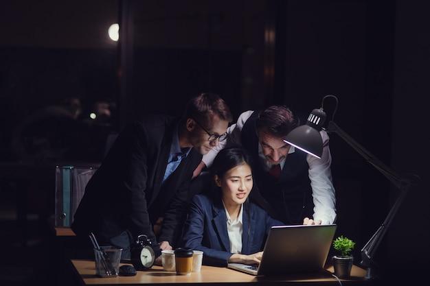 Gruppe verschiedenartigkeitsgeschäftsleute, die spät im büro nachts arbeiten. zwei kaukasische männer, die hinten stehen und das asiatische sekretärmädchen schreiben auf laptop mit tasse kaffee beraten
