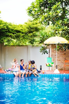 Gruppe verschiedene frauen, die durch das pool sitzen