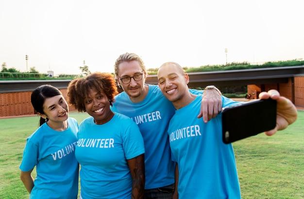 Gruppe verschiedene freiwillige, die zusammen selfie nehmen