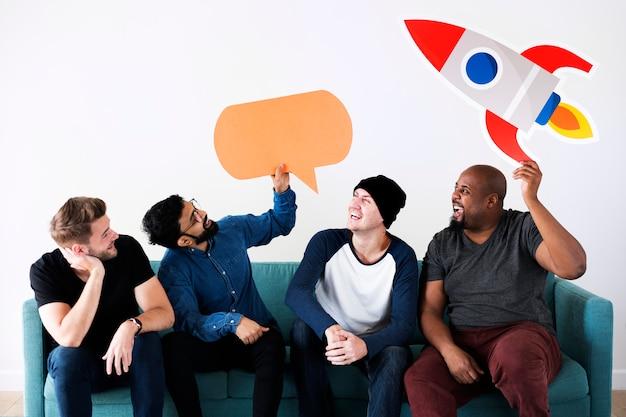Gruppe verschiedene freunde, die auf couch mit ikonen sitzen