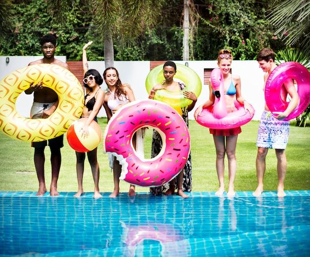 Gruppe verschiedene freunde, die den swimmingpool bereitstehen