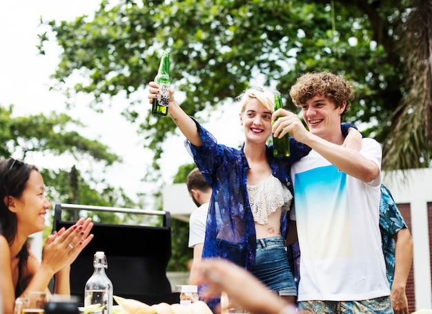 Gruppe verschiedene freunde, die zusammen klirrende biere feiern