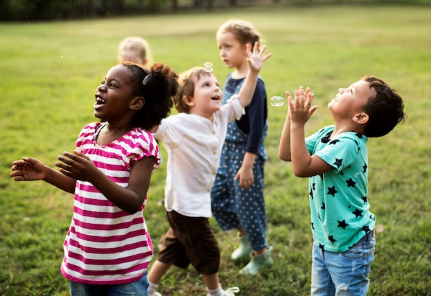 Gruppe verschiedene kinder, die zusammen am feld spielen