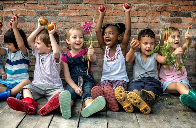 Gruppe verschiedene kinder, die zusammen mit frischgemüse sitzen