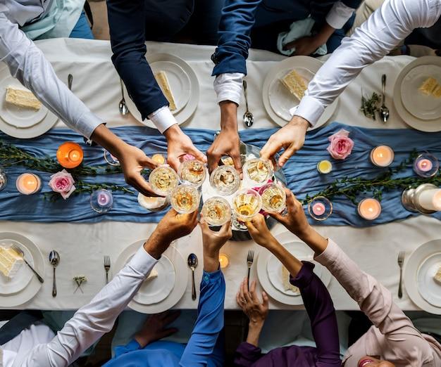 Gruppe verschiedene leute, die zusammen weingläser klirren glückwunsch-feier