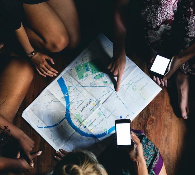 Gruppe verschiedene touristen, die auf der bretterbodenplanung auf der karte überprüfend sitzen