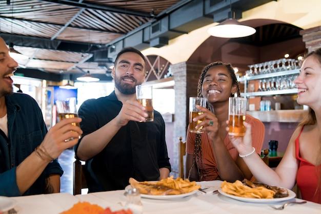 Gruppe verschiedener freunde, die bier trinken, während sie zusammen in einem restaurant eine mahlzeit genießen. freunde-konzept.