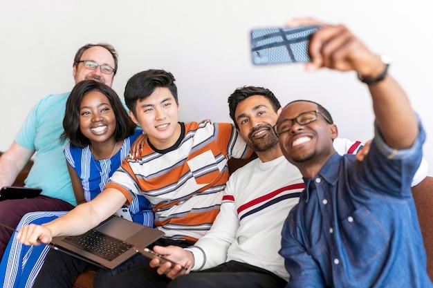 Gruppe verschiedener freunde, die ein selfie auf einer couch machen