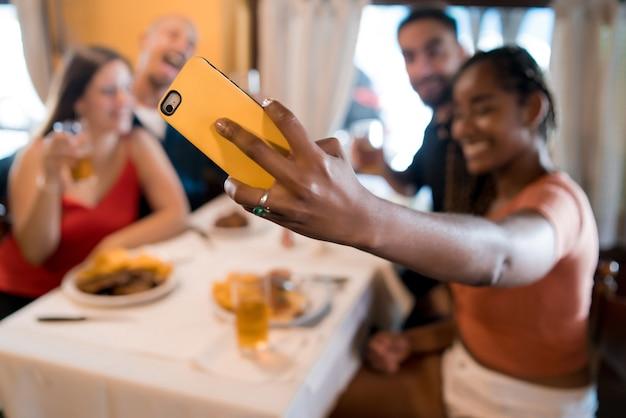 Gruppe verschiedener freunde, die ein selfie mit einem mobiltelefon machen, während sie gemeinsam in einem restaurant eine mahlzeit genießen. freunde-konzept.