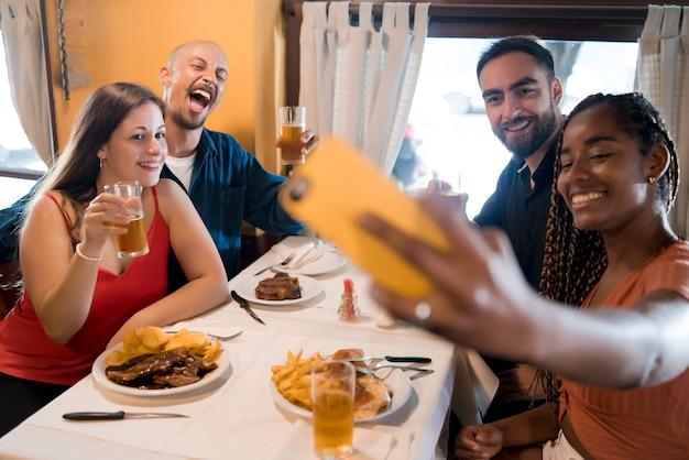Gruppe verschiedener freunde, die ein selfie mit einem mobiltelefon machen, während sie zusammen in einem restaurant eine mahlzeit genießen. freunde-konzept.