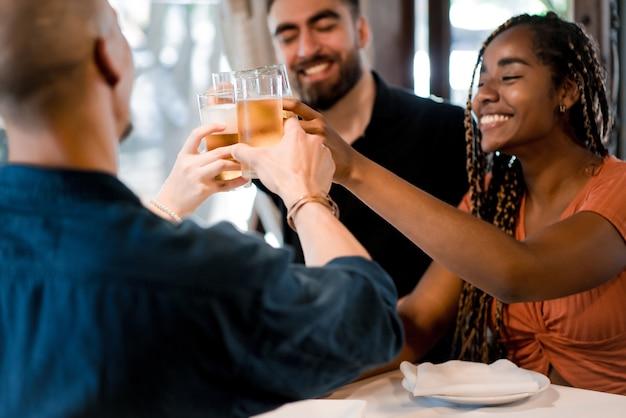 Gruppe verschiedener freunde, die mit biergläsern anstoßen, während sie gemeinsam in einem restaurant eine mahlzeit genießen. freunde-konzept.
