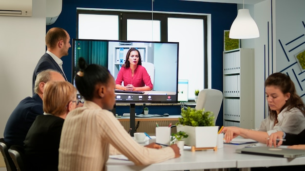 Gruppe verschiedener geschäftsleute, die mit einer kollegin über eine videokonferenz sprechen. remote-videoanruf-meeting, teamwork-online-brainstorming für mitarbeiter, virtuelles briefing in einem startup-bürounternehmen